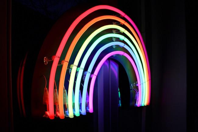 A neon rainbow lights up a dark wall.