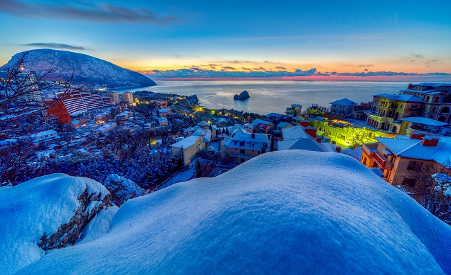A from a hill view, we see a snowy seaside town, lit by a colorful sunset. Why did Jesus come to earth? HE came to offer us all a hope in eternal life with His Father in heaven.