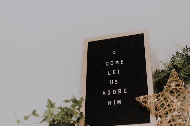 A letterboard displays the words 'o come let us adore Him'. Next to the board is a wire star and some evergreens. Jesus came when He did because it was God's perfect timing for the world.
