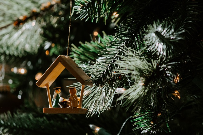 A wooden nativity tree ornament hangs from the lush green branch of a fresh Christmas tree. Jesus' arrival into the world as a baby meant that the people of the world could have a renewed hope.