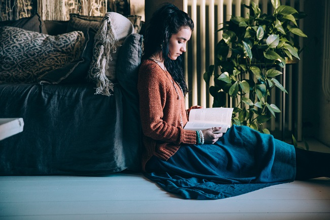 A young woman in a sweater and skirt, sits on the floor leaning up against a sofa. She is reading her Bible that is great for new believers!
