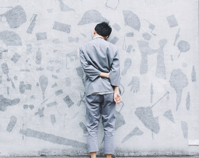 A man in a pale gray suit stands facing towards a gray-painted wall with his hands behind his back. His head leans up against the wall. If you need help with grief recovery, God can provide that help.