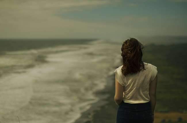 A woman walks along a beach. The lighting is dark and moody, with an unfriendly gray sky. God can help you in your grief with His 12 steps to Recovery.