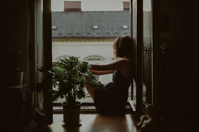 A woman sits on a windowsill and looks out of the open window with her legs tucked up and arms resting on her knees. Give God your struggles and He will answer with peace.