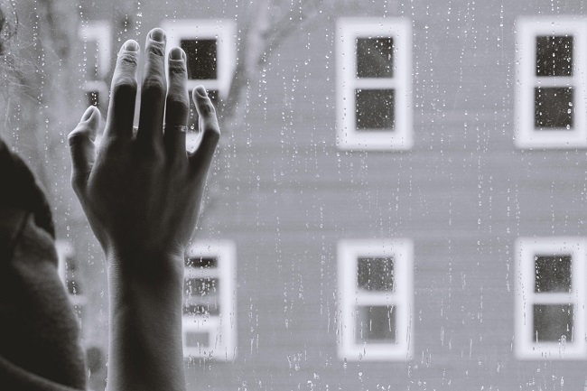 A gray-scale photo of a woman's hand on a glass pane, rain falls outside and the window looks out onto a building with lots of little windows. God can help you with recovery from your grief.