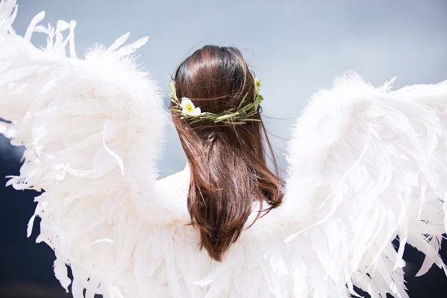 A brunette woman stands with her back to the camera, with a flower garland in her hair and white angel wings on her back. Will we be angels in Heaven? Randy Alcorn says no.