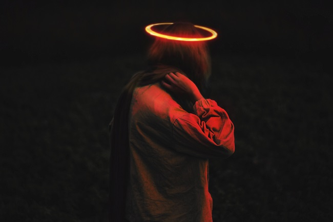 A young woman stands in a dark room with a red neon halo on her head. We can't see her face and her hand is placed by her neck. What will we all look like in Heaven? Probably not too dissimilar to how we look now!