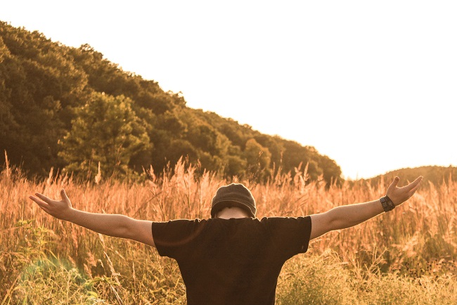 A young man in a t-shirt and beanie hat stands with his back to us, with his arms open wide and his palms facing upwards, he is in prayer.