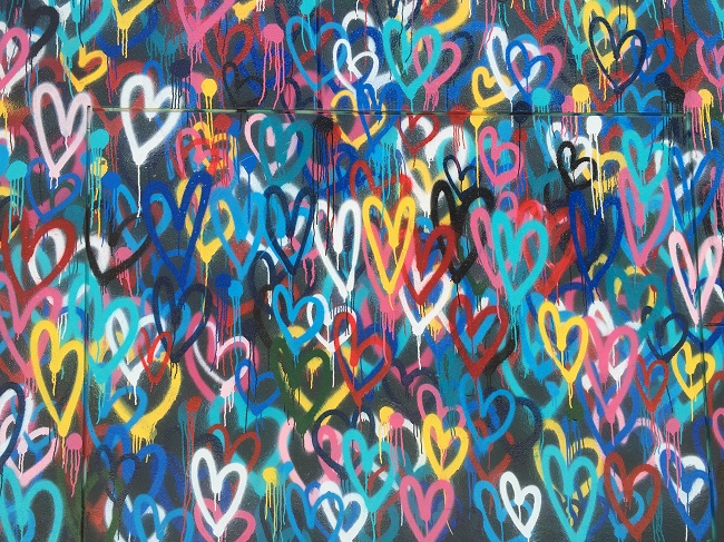 A wall of colorful and joyful graffiti hearts reminds us to be grateful and pray to God with gratitude every day.