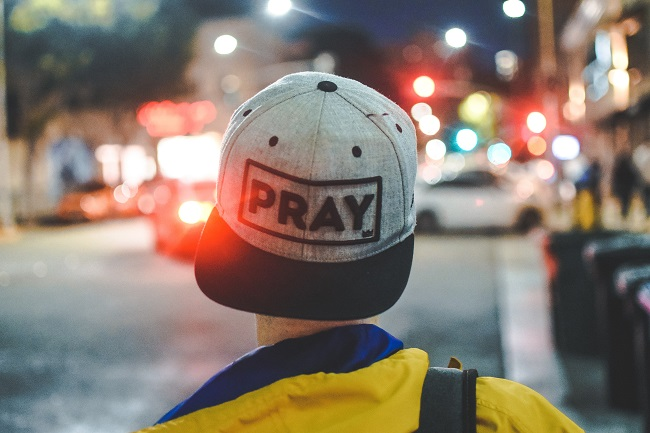 A young man is walking down the street with his cap on backwards, it says 'PRAY' on his hat.