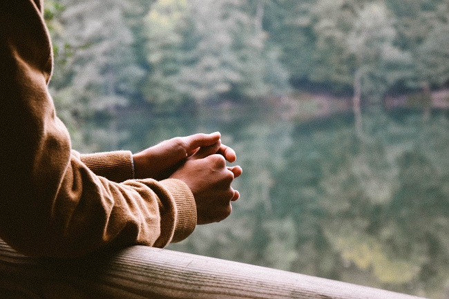 A man's hands can be seen in prayer, leaning on a balcony over-looking a beautiful river and tress on the other side.