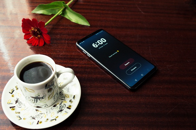 A smart phone sits on a dark wooden table with a full coffee cup and a flower laying next to it.