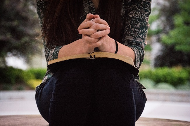 A woman sits with her hands clasped in prayer over her bible that lays on her lap.