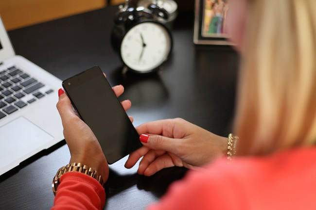 An office working woman holds her smart phone. We see an alarm clock near her and a computer too. She is learning how to make the Lord's Prayer, her prayer.