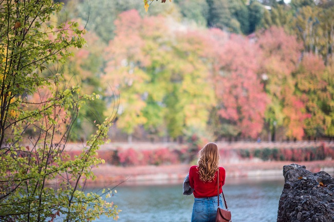 A woman stands by a lake surrounded by colorful early fall trees. Silence is an important part of prayer.