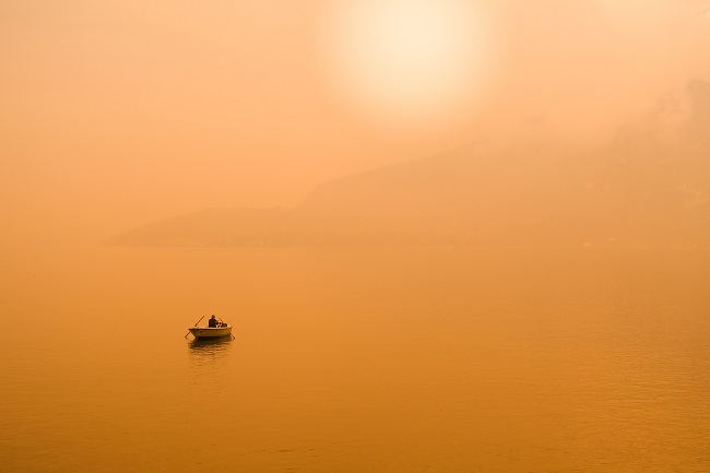 A small boat is seen way out on a lake that is bathed in hazey orange light.