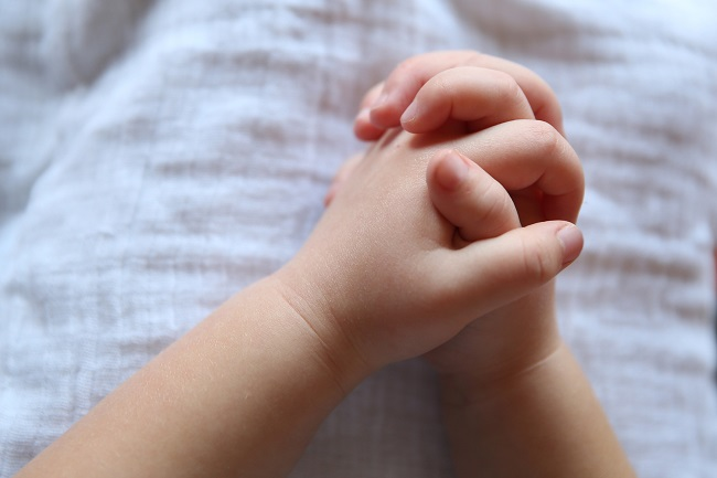 A small child's hands are clasped together in prayer. PRaying to God is so easy, children can do it!