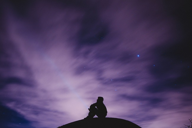 A person is seen in sillouette against a purple night sky. You can talk to God like you would any friend. Prayer doesn't need to be hard or complicated.