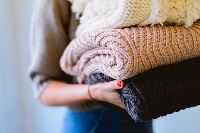 A woman holds a small pile of thick blankets for donation.