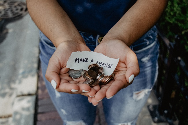 A pair of hands hold out change and a note that says 'make a change'.