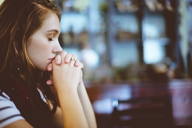 A young woman prays to God in a sitting position, inside a church.