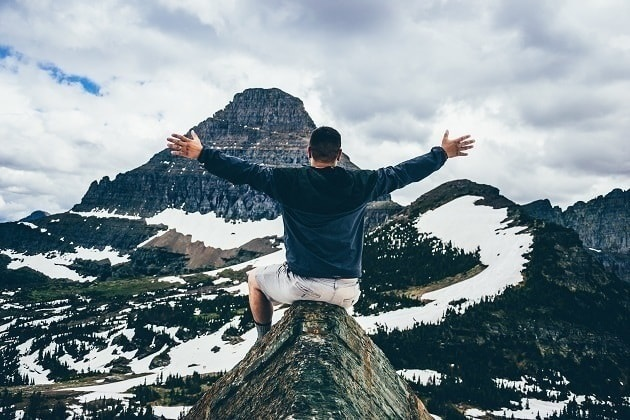 A joyful man sits atop a snowy mountain peak with a large mountain ahead of him.