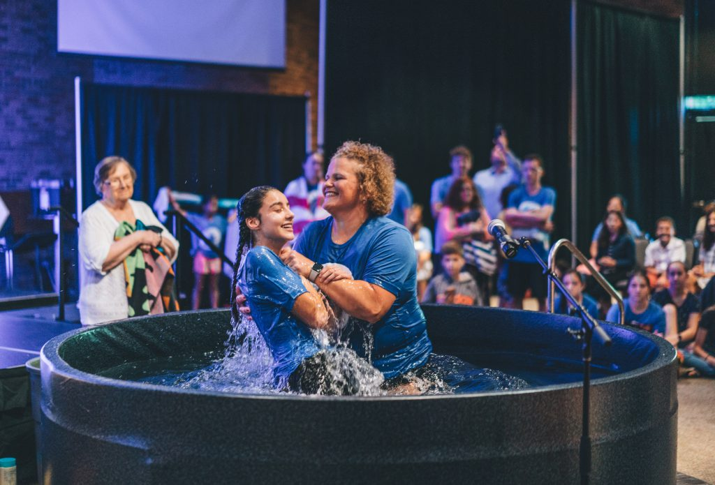 A teenage girl emerges from baptism waters at her church. She is smiling.