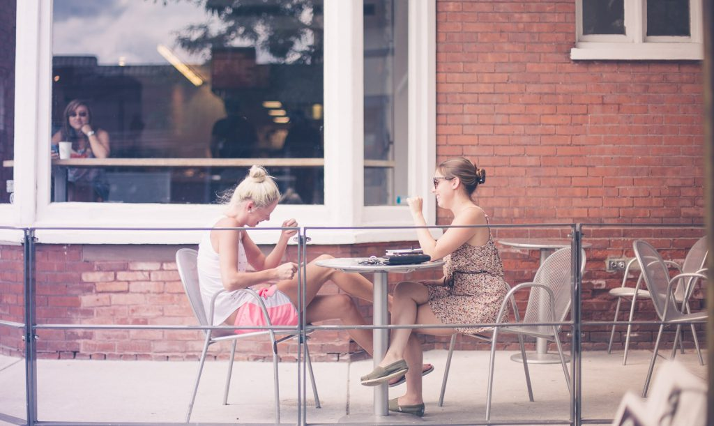 Two women sit at outside a cafe laughing, having a spiritual conversation.