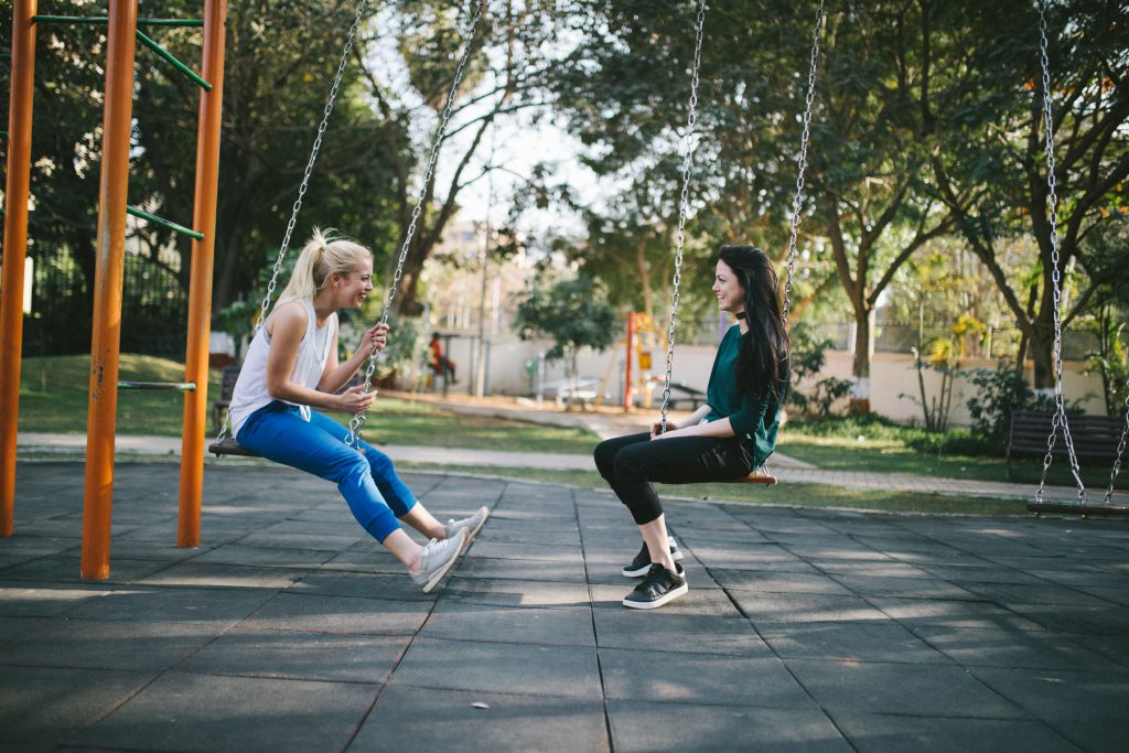 Young ladies hang out and chat about faith on park swings.