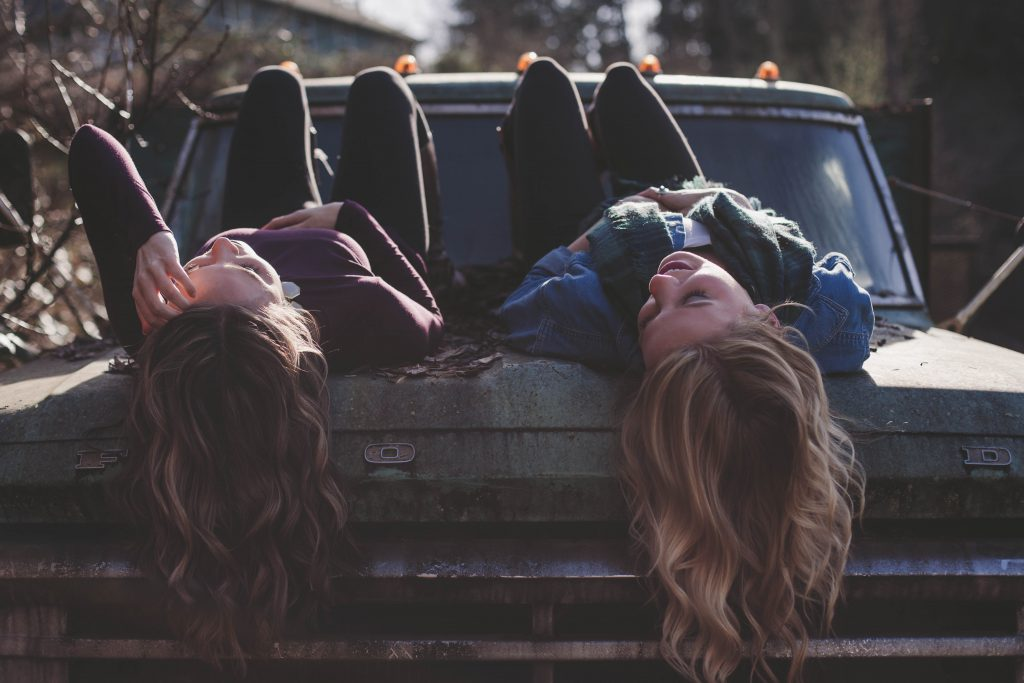 Two women chat about faith while hanging out on a truck hood.