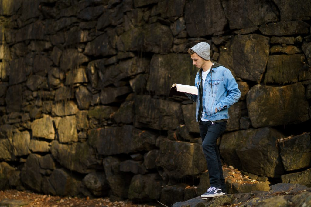 A young man with a denim jacket and beanie reads the Bible in front of an old stone wall. He loves his Bible study.