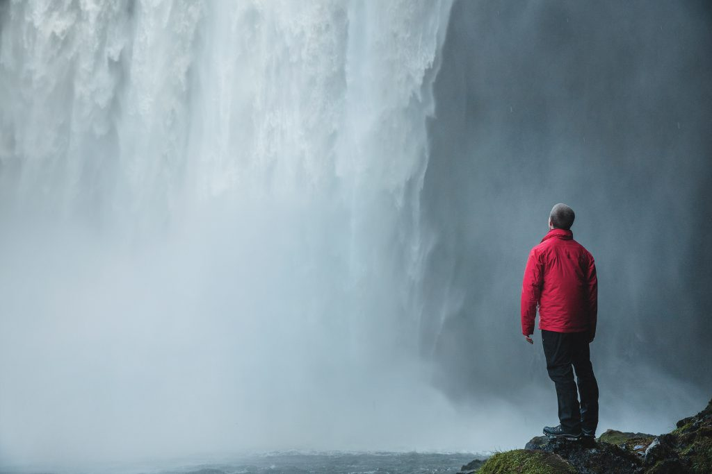 A man stands beside a waterfall. depicting the freedom found in recovery through Jesus. Devotionals for new believers.