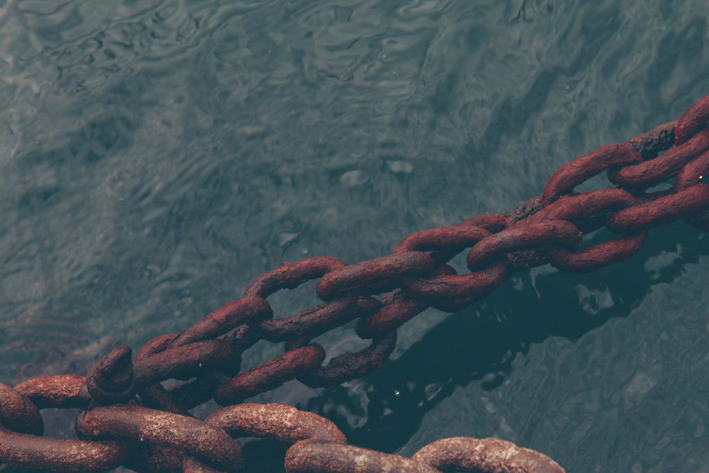 Is there anything God is willing to forgive? Rusty chains stand taught over dark water.