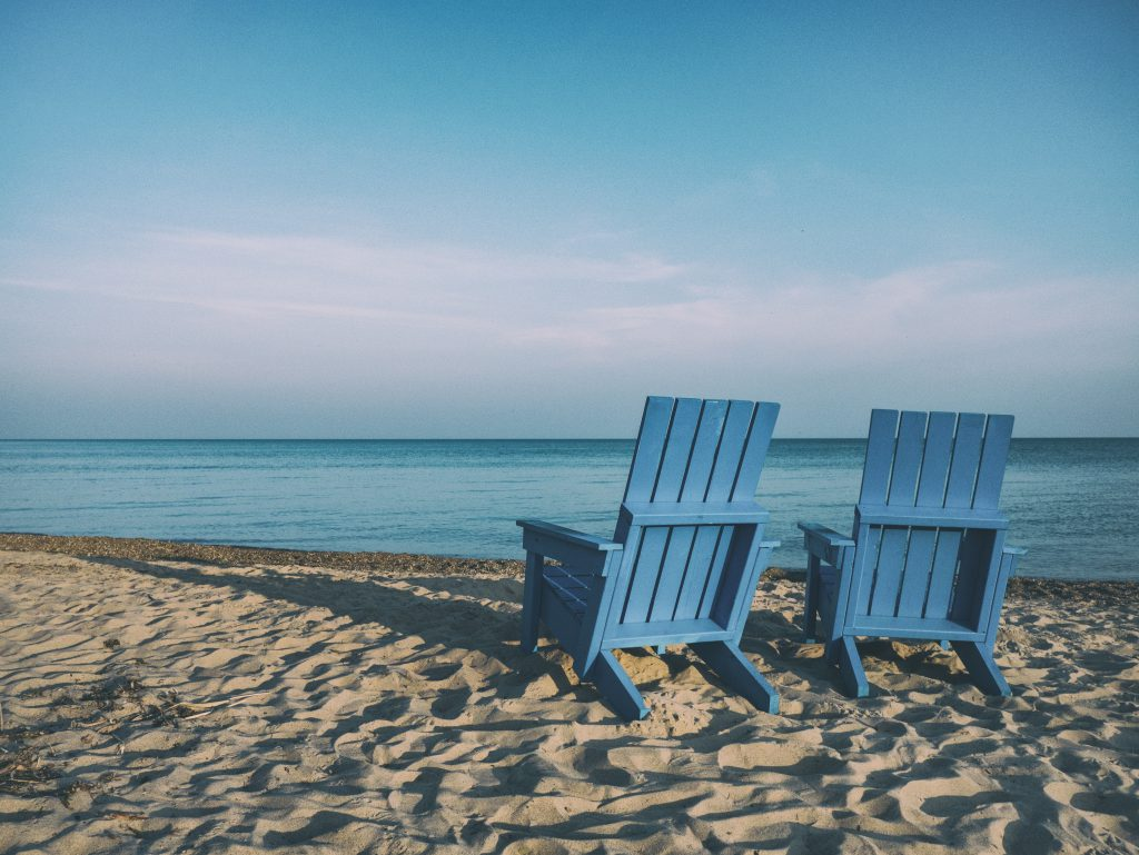 Empty beach chairs as the sun gets low behind them. Talk about your testimony with others.