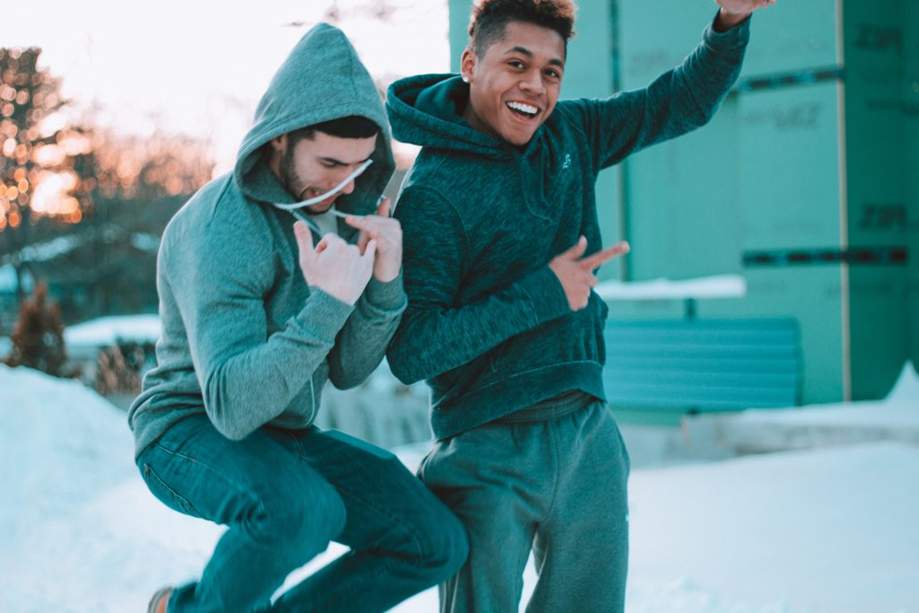 Two male friends jump around being goofy. Happy, they celebrate their testimonies!