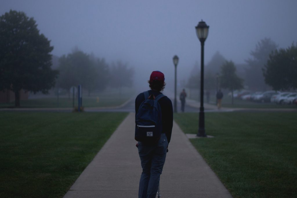 A male student stands in a gloomy, misty morning light. Share your testimony.