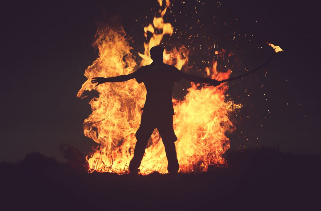 Man stands in front of a very large fire he has started. Aggression is part of this testimony.