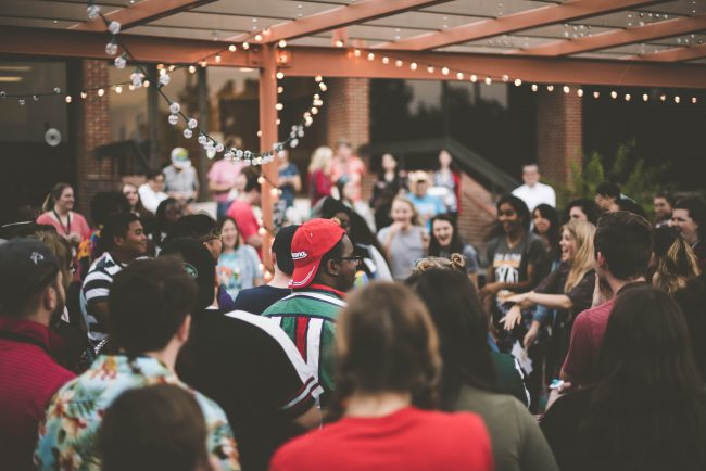 A large group of diverse people enjoy a party in an outside event space. Could you have the gift of hospitality? Do you enjoy organizing events? Answer questions to discover your life purpose.