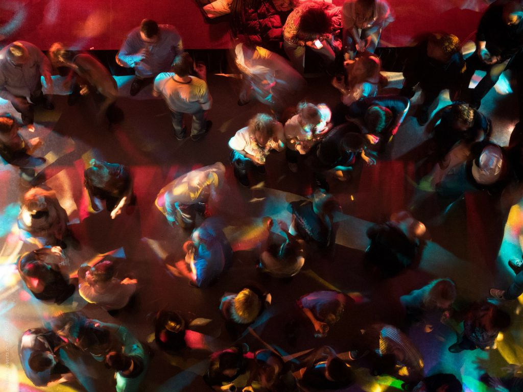 People fill up a space in a bar as they dance, chat and drink together. Celebrating with Christmas outings, parties and work parties is perfectly okay as a new believer in Jesus.