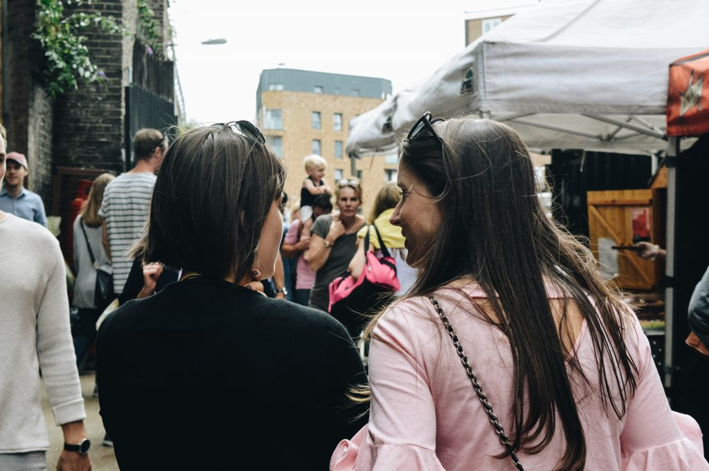 Two women walk arm in arm through a street market, we see them from the back and can see that they are talking happily about Jesus.