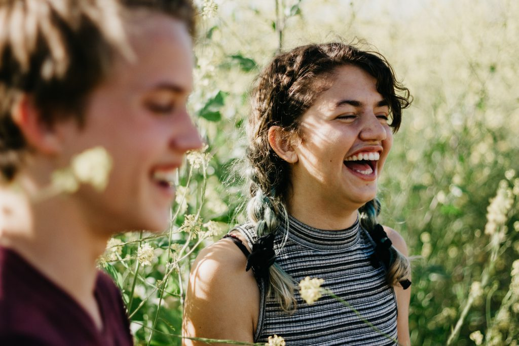 A teenage girl and boy stand in a sunny meadow laughing. They know the jot there is in talking about, and sharing, Jesus with their non-believer friends.