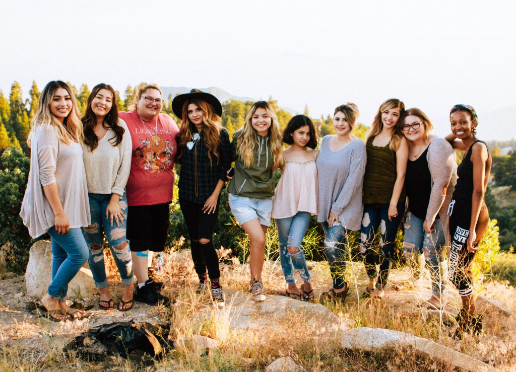 A group of 10 women stand and smile together taking a group picture. They make up an example of a strong small group.