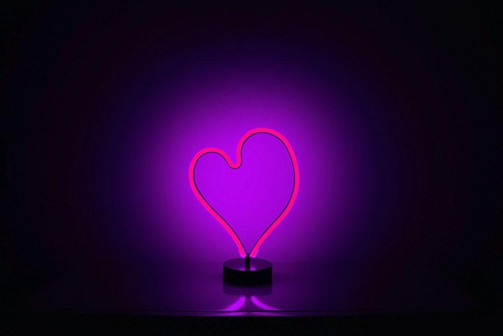 Lament says we can have an intimate and even more loving relationship with God. A neon purple heart lights up a bare wall behind it in the dark.