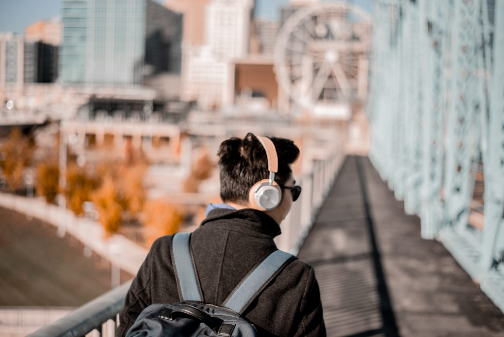 An Asian man walks across a bridge in a large city, with headphones on and listening to a podcast.