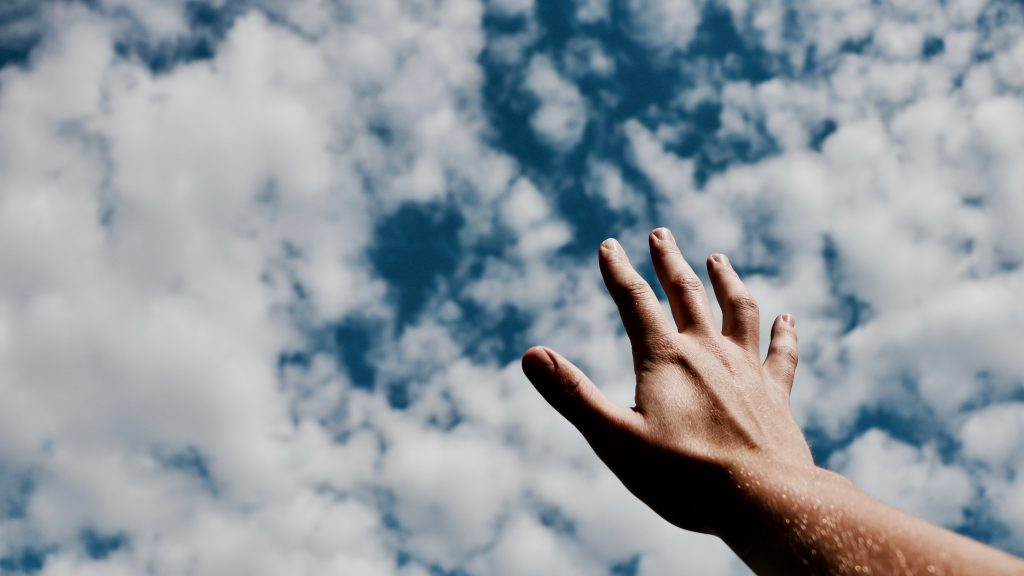 Lament prayers offer us relief. A hand reaches up to a blue sky with clouds.