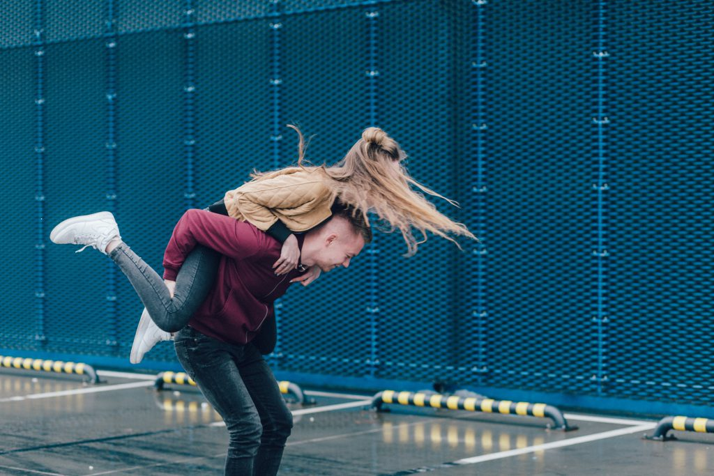 A young couple play around with the woman jumping on the man's back. A change in our own heart can help us improve our love relationships.