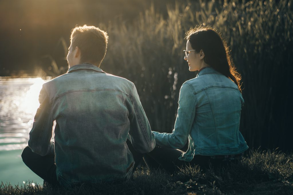 A couple sit holding hands beside a small river with the sun gently lighting them. How can we improve our relationships? By improving ourselves, with God's help.