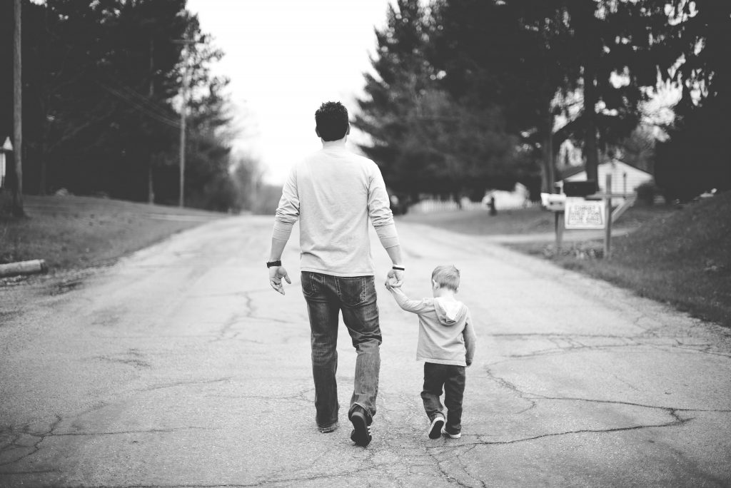 A black and white shot of a father and son holding hands as they walk down a cracked road with trees on either side of them and buildings ahead of them. Effective fathers of faith fight for their families.
