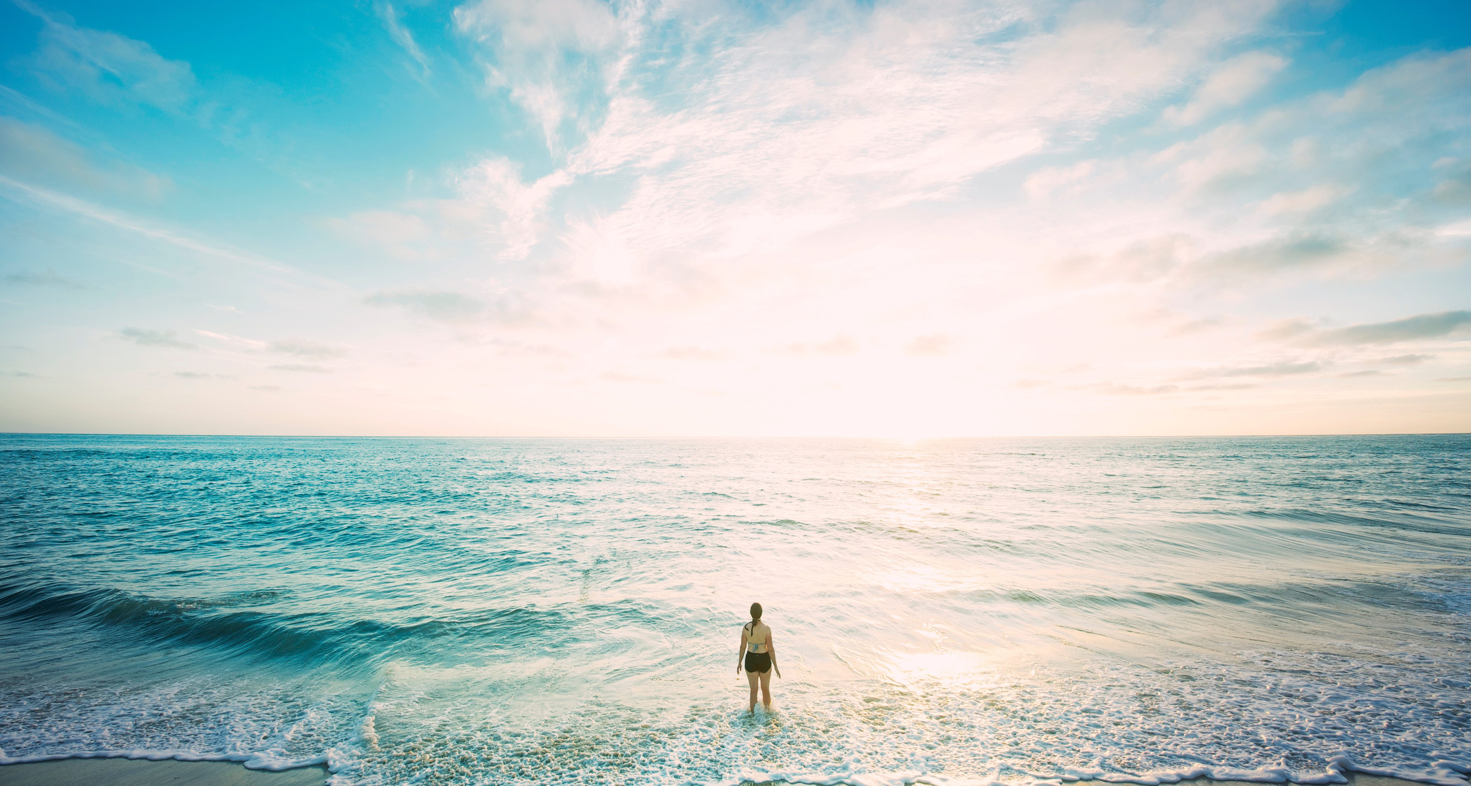 A woman in a swim suit stands within the water's edge on a beach. The sun is rising on the horizon and fills the background with light, making the beautiful blue and purple ocean look both inviting and endless. Much like God's promises, which are also inviting and endless. Here's how you can start relying on God's promises.