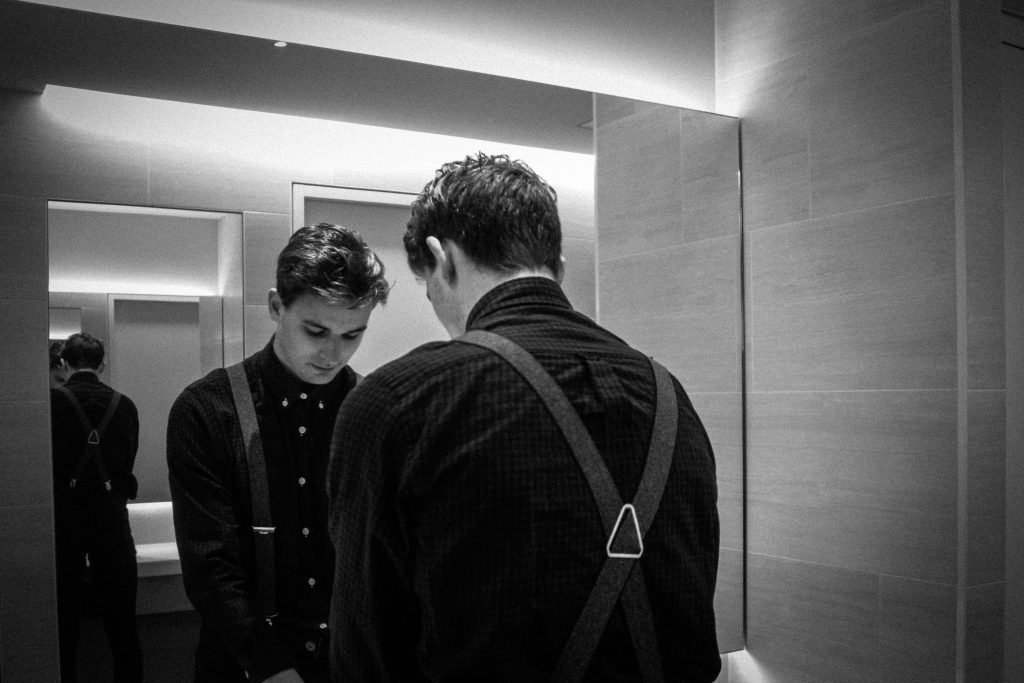 A young man dressed for a night out stands in front of a smart bathroom mirror with his head bowed as he looks down. Reading the Word of God everyday can help us to start relying on God's promises.